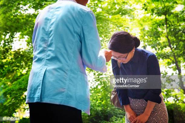 female japanese office worker bows after offering business card - humility stock pictures, royalty-free photos & images