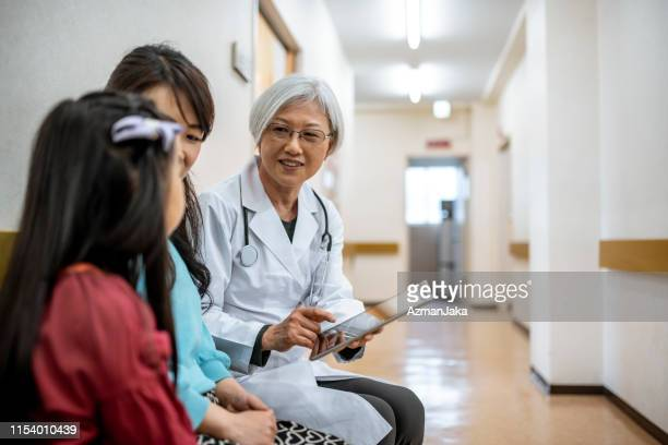 female japanese physician meeting with mother and daughter - medical chart stock pictures, royalty-free photos & images