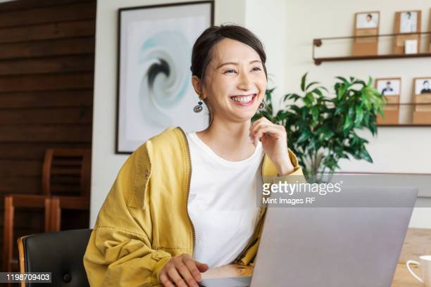 female japanese professional sitting at a table in a co-working space, using laptop computer. - 30代 ストックフォトと画像