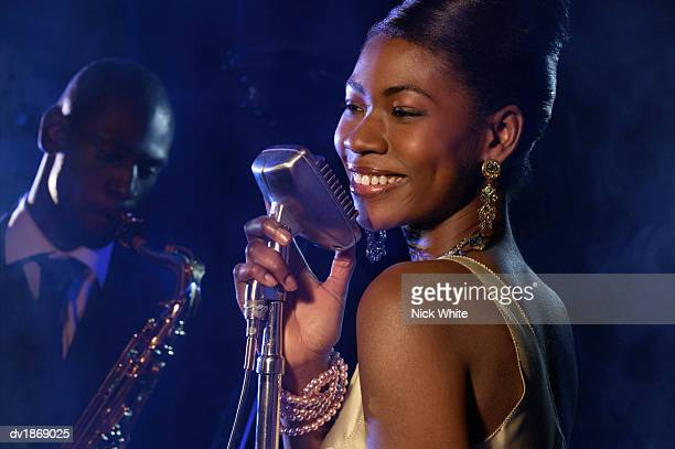 female jazz singer standing with a microphone in front of a man playing an alto saxophone - beehive hair stock pictures, royalty-free photos & images
