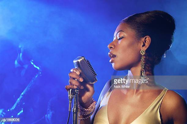 female jazz singer standing with a microphone in front of a man playing an alto saxophone - jazz stock pictures, royalty-free photos & images