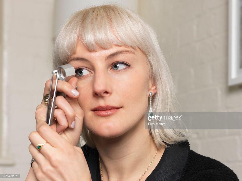 Female jeweler examining diamond using magnifier in jewellery shop : Stock Photo