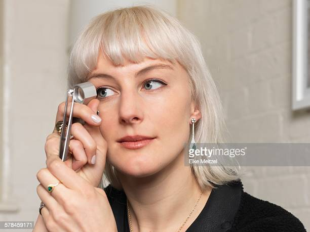 Female jeweler examining diamond using magnifier in jewellery shop