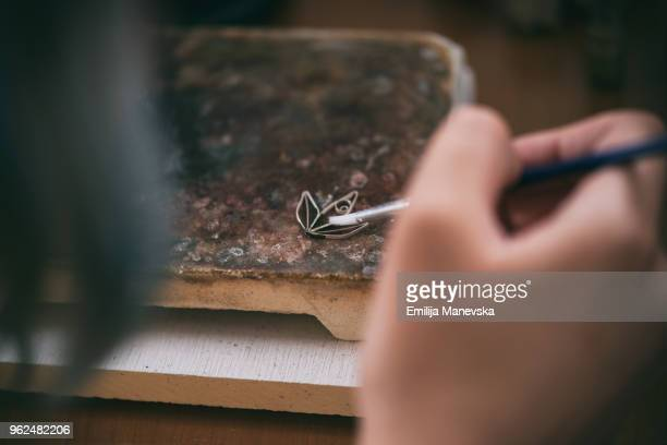 female jeweler making silver jewelry in workshop - jeweller stock photos and pictures