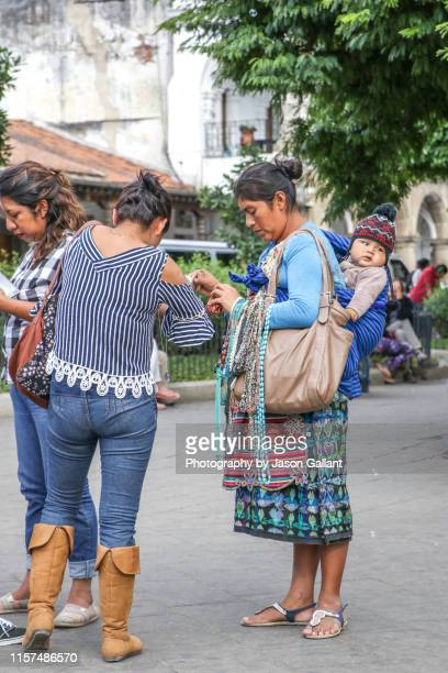 female jewelry vendor selling necklaces while carrying her baby in the plaza central park in antigua, guatemala - guatemala city stock pictures, royalty-free photos & images