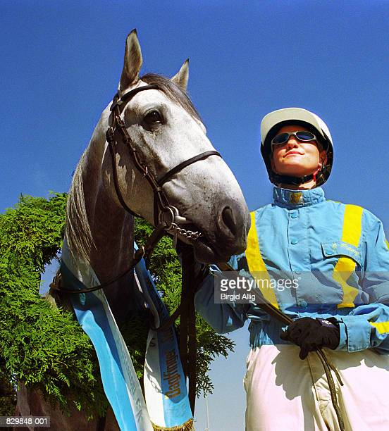 Female jockey standing with horse wearing sash, close-up