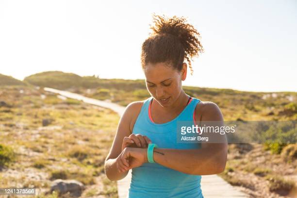 female jogger checking her time while out for a run in nature - active lifestyle stock pictures, royalty-free photos & images
