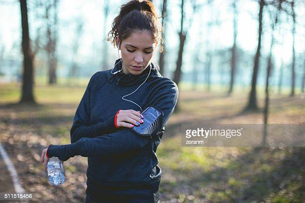 Female jogger choosing music from smart phone