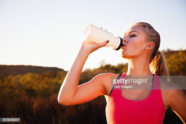 Female jogger drinking from water bottle, Poway, CA, USA
