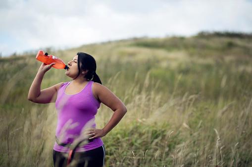 Female jogger drinking water from bottle - gettyimageskorea