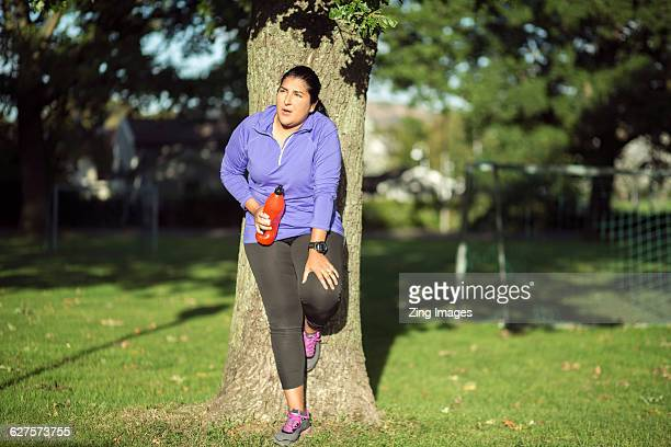 female jogger leaning against tree - fat lady in leggings stock photos and pictures