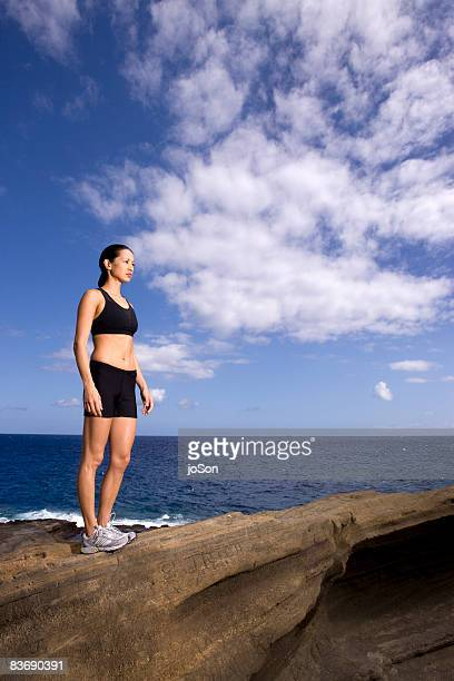 Female jogger looking out at ocean, Hawaii