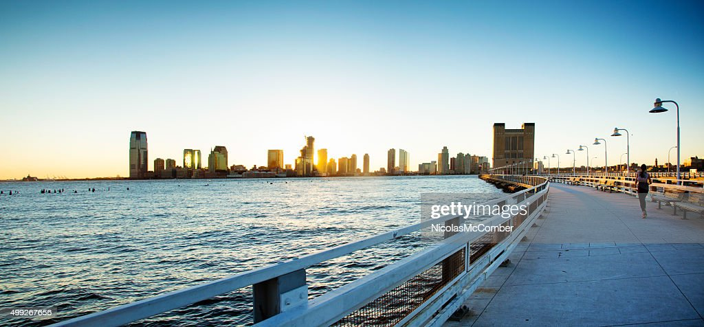 Female jogger on Manhattan pier with Jersey City and sunset : Stock Photo