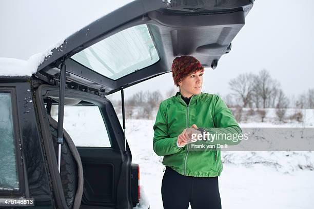 Female jogger preparing for run in snow covered scene