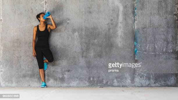 female jogger resting - leaning stock pictures, royalty-free photos & images