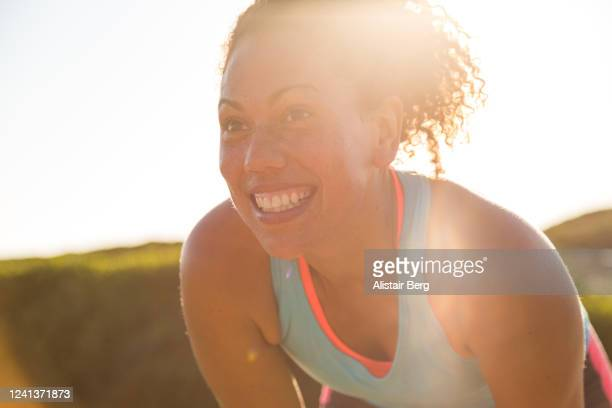 female jogger resting while out for a run in nature - active lifestyle stock pictures, royalty-free photos & images