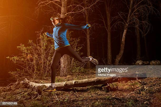 Female jogger running in forest at night