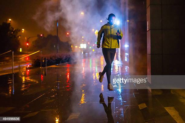 Female jogger running on rainy night in the city