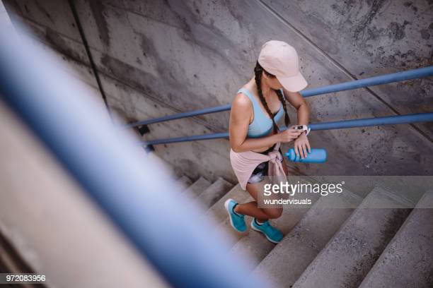 Female jogger running up stairs and checking time on smartwatch