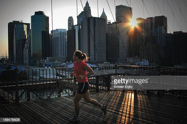 CONTENT] A female jogger runs across Brooklyn Bridge during sunset on a summer evening in New York City