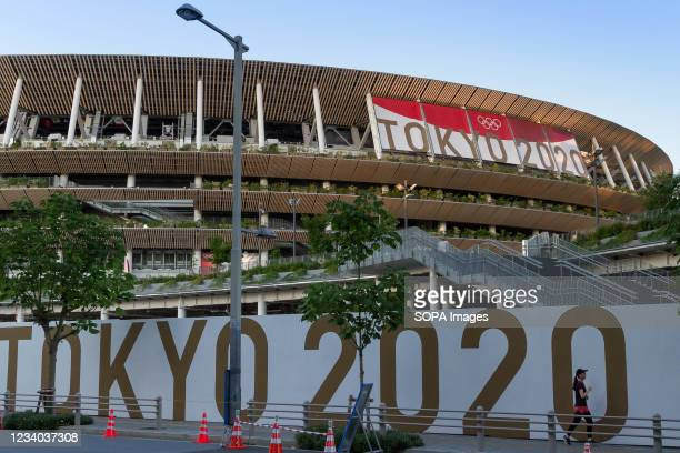 Female jogger runs around the 2020 Tokyo Olympic National Stadium, Gaiemmae. The delayed 2020 Tokyo Olympics is set to open on July 23rd 2021 despite...