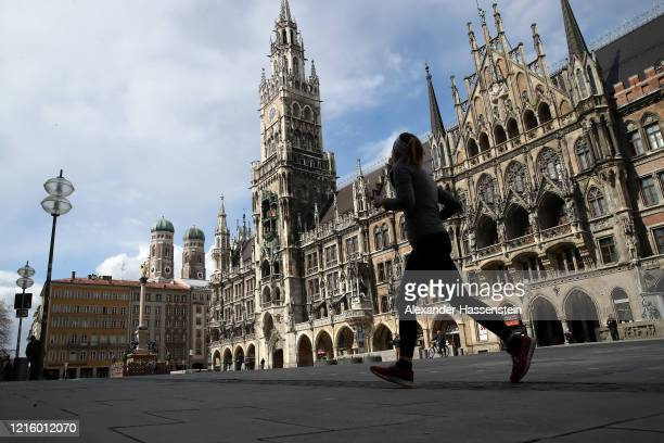 A female jogger runs over the empty Marienplatz with the Townhall of Munich during the coronavirus crisis on March 31 2020 in Munich Germany Public...