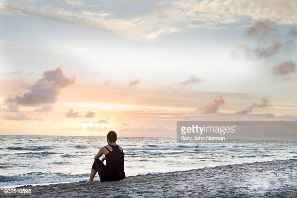 Female jogger sits on beach watching the sunrise