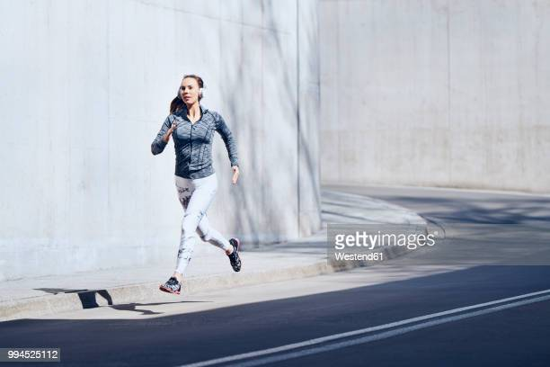 female jogger with headphones on street - track event stock pictures, royalty-free photos & images