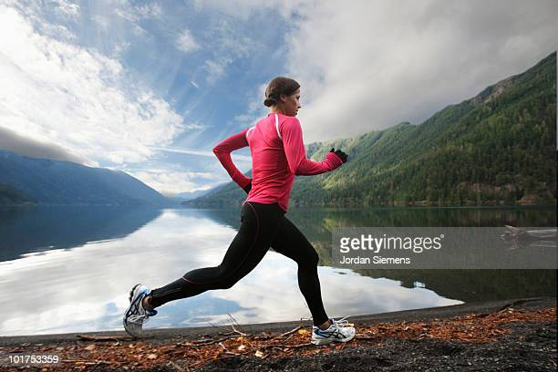 a female jogging along the lake crescent shore. - cross country running stock pictures, royalty-free photos & images