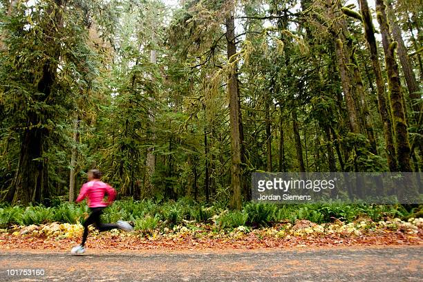 A female jogging down a road next to tall trees covered in moss.