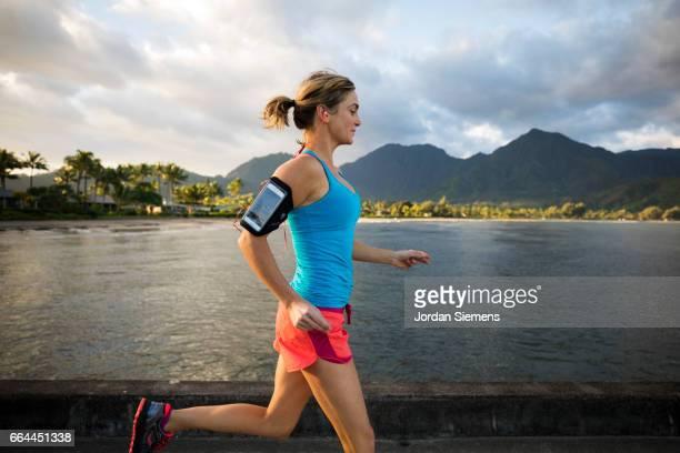 A female jogging near the ocean.