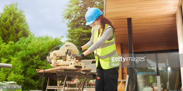 female joiner cutting cladding - circular saw stock photos and pictures