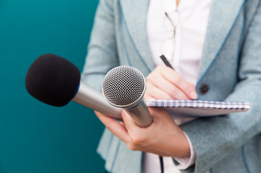 Female journalist at press conference, writing notes, holding microphone 890868308