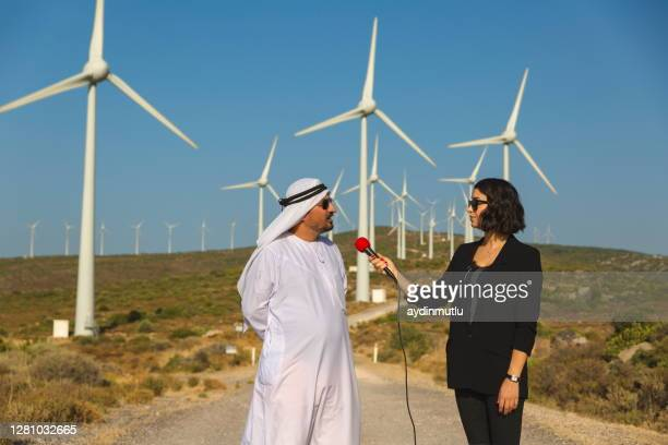 female journalist interviews arab businessman in wind turbines - journalist stock pictures, royalty-free photos & images