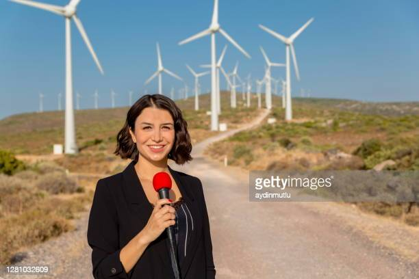 female journalist presents live broadcast on wind turbines - journalist stock pictures, royalty-free photos & images