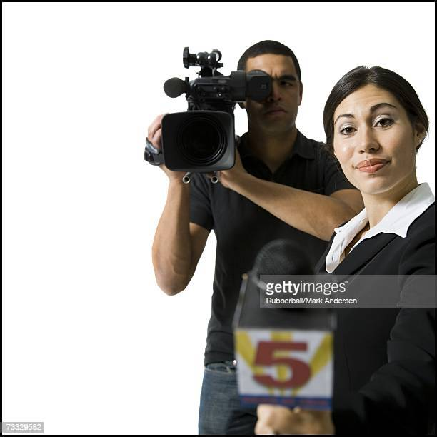 female journalist with microphone and male videographer - photojournalist stock pictures, royalty-free photos & images