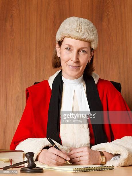 Female judge sitting at desk, smiling, portrait, close-up