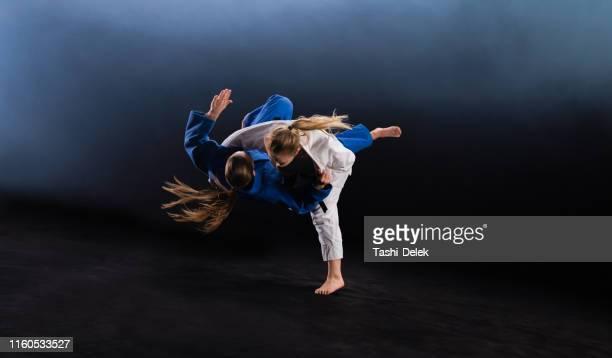 女性柔道家がパートナーを地面に投げ捨てる - 柔道 ストックフォトと画像