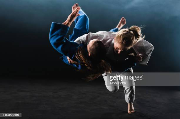 female judoka throwing her partner to the ground - martial arts stock pictures, royalty-free photos & images