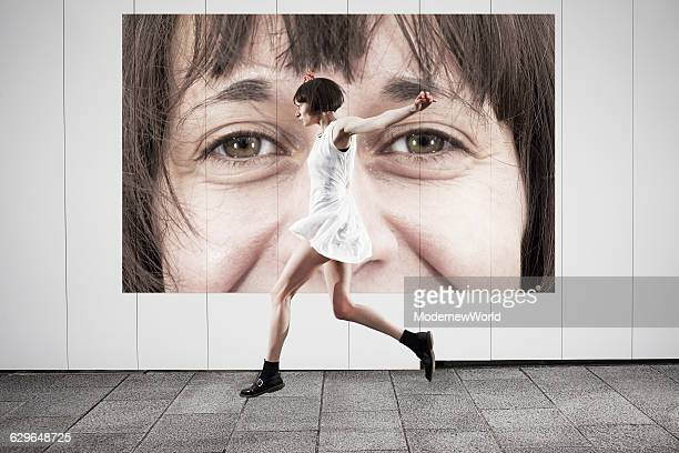 A female jumping in front of her own poster