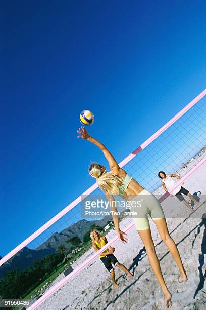 Female jumping to hit volleyball over net