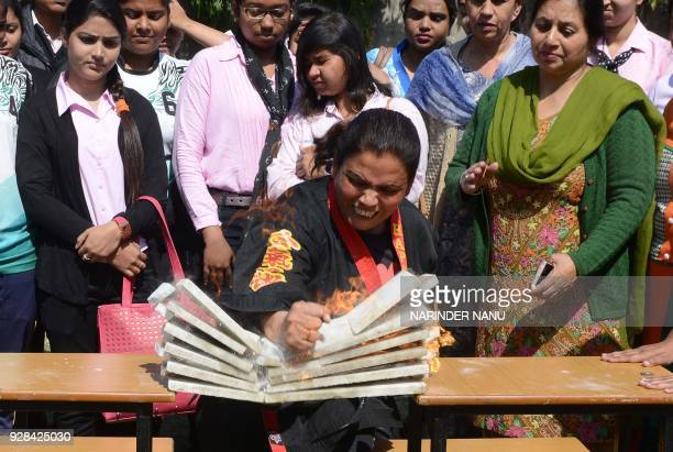 TOPSHOT A female karate exponent demonstrates her skills on the eve of the International Women's Day in Amritsar on March 7 2018 / AFP PHOTO /...