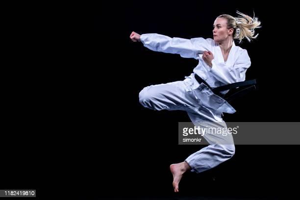 jugadora femenina de karate saltando en el aire para patadas - artes marciales fotografías e imágenes de stock
