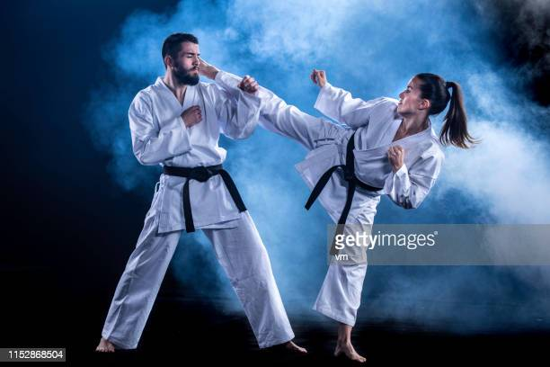 female karateka doing a turning kick on male sparring partner - martial arts stock pictures, royalty-free photos & images