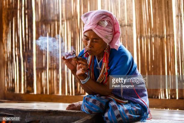 Female karen hill tribe is smoking tobacco pipe