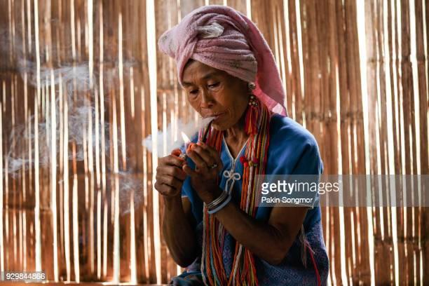 Female karen hill tribe is smoking tobacco pipe.