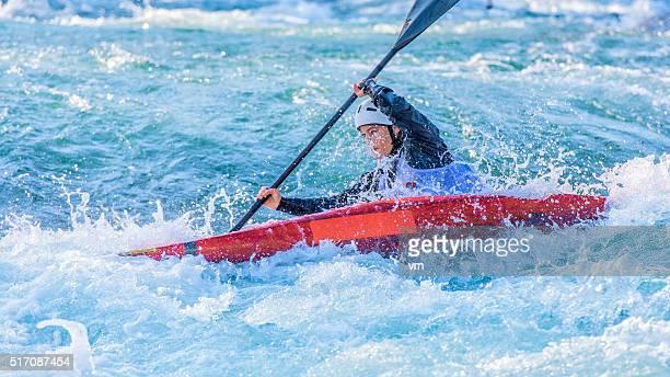 Weibliche Kajakfahrer paddeln im Whitewater