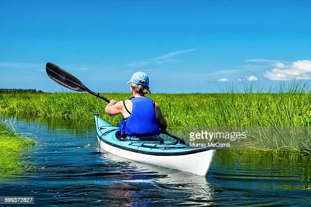 Female kayaker winding through salt marsh