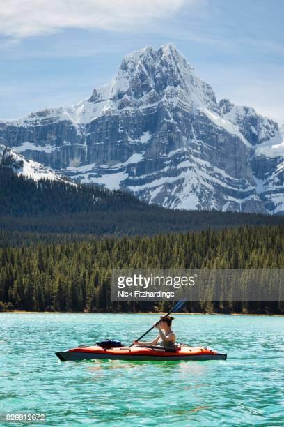 Female kayaking on Upper Waterfowl lake beneath Howse Peak in the Canadian Rockies, Banff National Park, Alberta, Canada