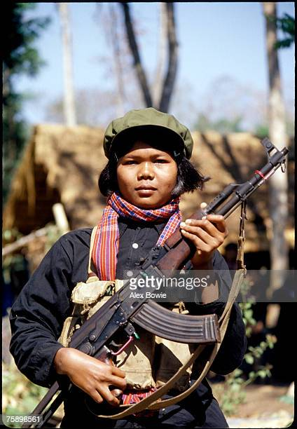 Female Khmer Rouge fighter or 'mit naree' carries an AK-47 assault rifle in the jungle of western Cambodia, 15th February 1981.